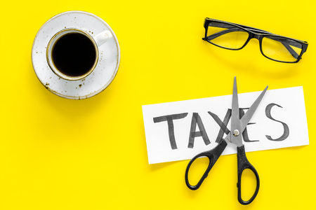 Tax reduce concept. Scissors and paper with word Taxes on yellow background with coffee and glasses top view. Фото со стока