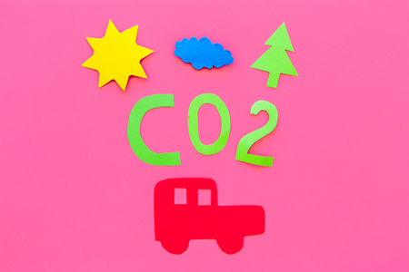 Car pollutes the environment by carbon dioxide. Car, environment and CO2 cutout on pink background top view. Imagens