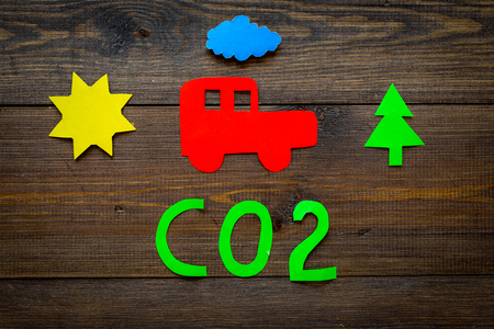 Car pollutes the environment by carbon dioxide. Car, environment and CO2 cutout on dark wooden background top view.