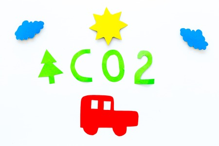 Car pollutes the environment by carbon dioxide. Car, environment and CO2 cutout on white background top view.