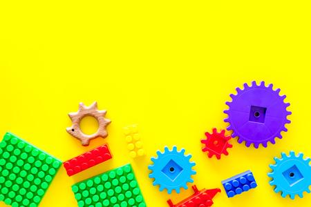 Developing children games mockup. Colorful plastic bricks and blocks on yellow background top view. 版權商用圖片