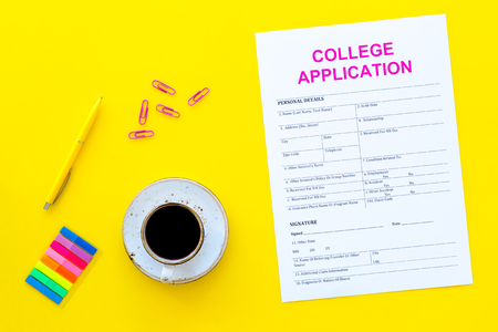 Higher education. College application form ready to fill near coffee cup and stationery on yellow background top view.
