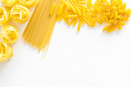 Set of pasta. Raw spaghetti, fusilli, penne, fettuccine on white background top view. 写真素材