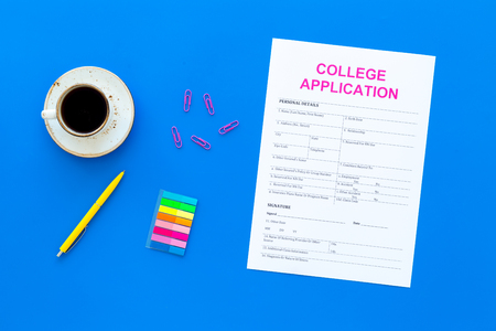 Higher education. College application form ready to fill near coffee cup and stationery on blue background top view. Banque d'images - 103515324