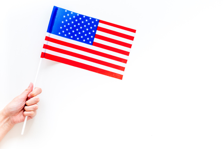 American flag concept. Hand hold small flag on white background top view.