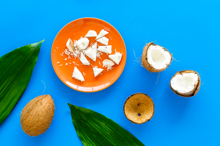 Pieces of coconut flesh on plate on blue background with coconut cut in half and palm leaves top view. 写真素材