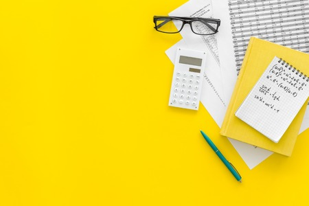 Math homework. Math textbook or tutorial near sheet with numbers, counts, calculator, notebook with formula on yellow background top view. Stock Photo