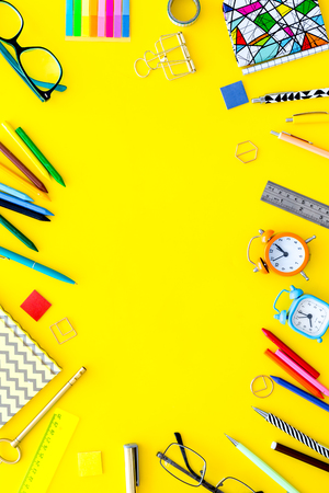 Education background, frame. School, student, office supplies. Stationery, glasses, alarm clock notebook on yellow background top view