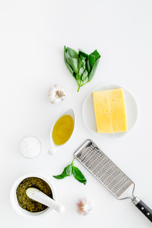 Cook homemade pesto sauce. Cheese, garlic, green basil, olive oil, salt near grater and mortar on white background top view copy space
