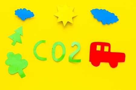 Car pollutes the environment by carbon dioxide. Car, environment and CO2 cutout on yellow background top view Stock Photo