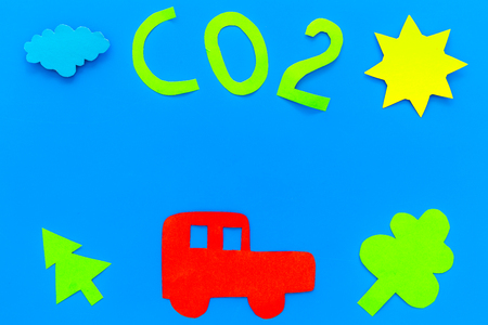 Car pollutes the environment by carbon dioxide. Car, environment and CO2 cutout on blue background top view copy space