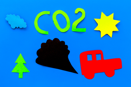 Cars emitting carbon dioxide. Pollution concept. harm the environment. Car and smoke cutout on blue background top view