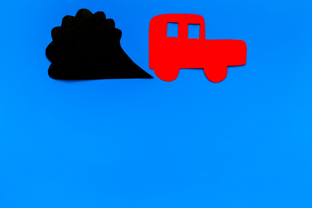 Car emitting dirty smoke. Pollution concept. Car and smoke cutout on blue background top view copy space