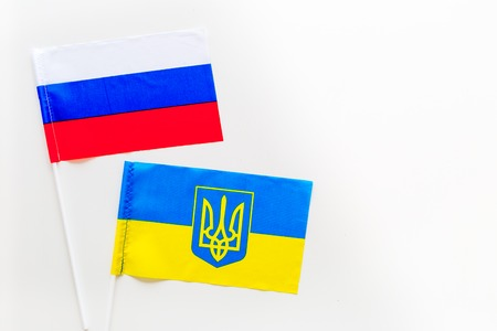 Russia-Ukraine relations. Country cooperation. Russian and Ukrainian flags on white background top view copy space