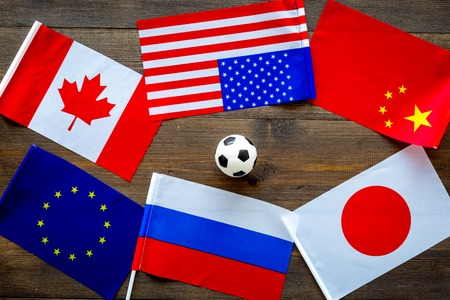 Football championship. American, Canadian, European, Japanese, China, Russian flags and football ball on dark wooden background top view Reklamní fotografie