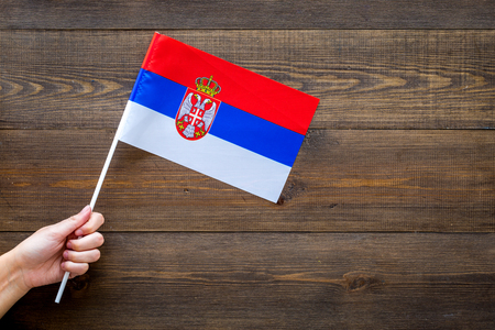 Serbian flag concept. Hand hold small flag on dark wooden background top view copy space