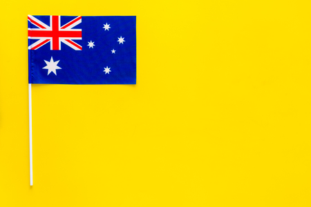 Australian flag concept. Small flag on yellow background top view copy space