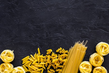 Set of pasta frame. Uncooked spaghetti, fusilli, penne, fettuccine on black background top view. 스톡 콘텐츠