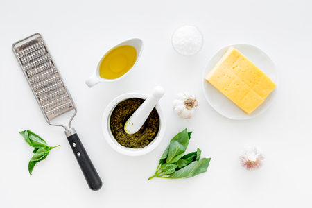 Ingredients for pesto sauce. Cheese, garlic, green basil, olive oil, salt near grater and mortar on white background top view. Stockfoto