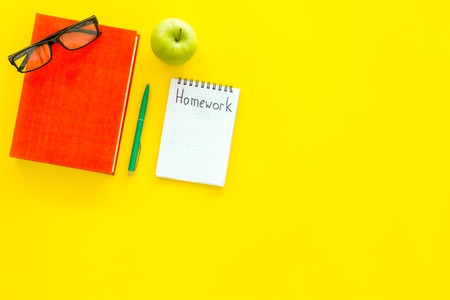 Homework concept. Word homework written in notebook on yellow desk with textbooks, tutorials and apple top view.