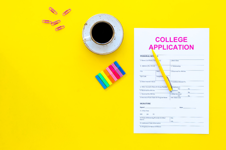 Apply college. Empty college application form near coffee cup and stationery on yellow background top view.