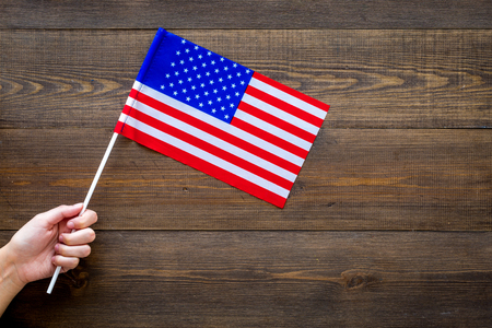 American flag concept. Hand hold small flag on dark wooden background top view.