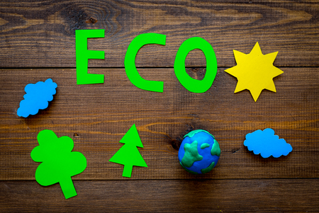 Eco icon cutout near plasticine symbol of planet earth and environment as sun, trees, clouds on dark wooden background top view. Imagens