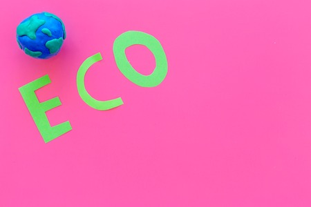 Eco icon cutout near planet earth plasticine symbol on pink background top view.