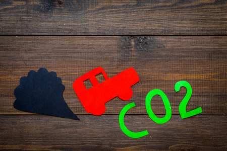 Car exhaust, CO2, smoke. Car and smoke cutout on dark wooden background top view Stock Photo