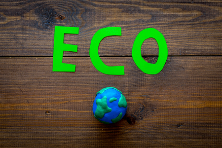 Eco icon cutout near planet earth plasticine symbol on dark wooden background top view.