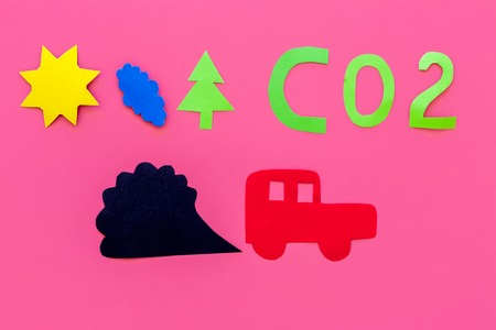 Cars emitting carbon dioxide. Pollution concept. harm the environment. Car and smoke cutout on pink background top view. Stock Photo