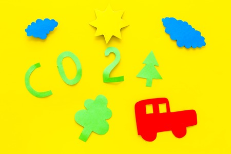 Car pollutes the environment by carbon dioxide. Car, environment and CO2 cutout on yellow background top view. Stock Photo