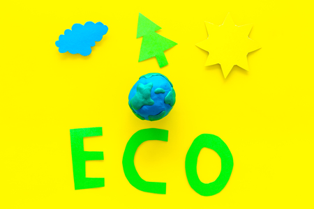 Eco icon cutout near plasticine symbol of planet earth and environment as sun, trees, clouds on yellow background top view.