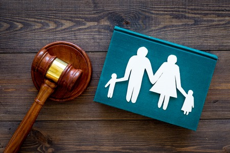 Family law, family right concept. Child-custody concept. Family with children cutout near court gavel on dark wooden background top view. Stockfoto - 103681726