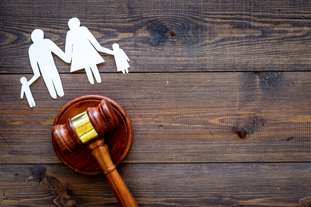 Family law, family right concept. Child-custody concept. Family with children cutout near court gavel on dark wooden background top view. Stockfoto - 103681727