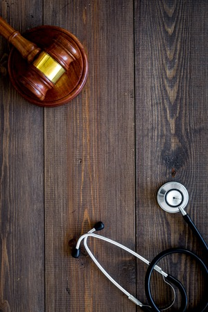 Medical law, health law concept. Gavel and stethoscope on dark wooden background top view. Фото со стока