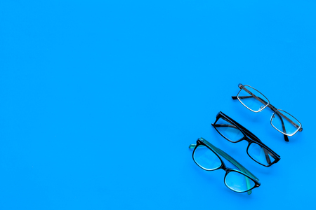 Glasses concept. Set of glasses with different eyeglass frame and transparent lenses on blue background top view. Stock Photo - 103681656