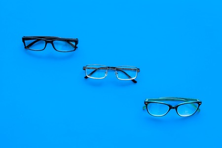 Glasses concept. Set of glasses with different eyeglass frame and transparent lenses on blue background top view. Reklamní fotografie - 103681660