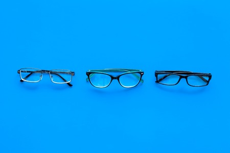 Glasses concept. Set of glasses with different eyeglass frame and transparent lenses on blue background top view.