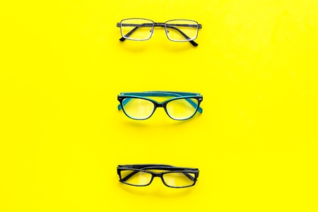 Glasses concept. Set of glasses with different eyeglass frame and transparent lenses on yellow background top view. Stock Photo - 103681667
