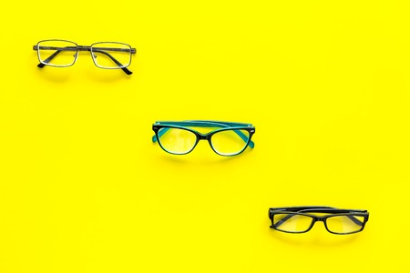 Glasses concept. Set of glasses with different eyeglass frame and transparent lenses on yellow background top view. Reklamní fotografie - 103681662
