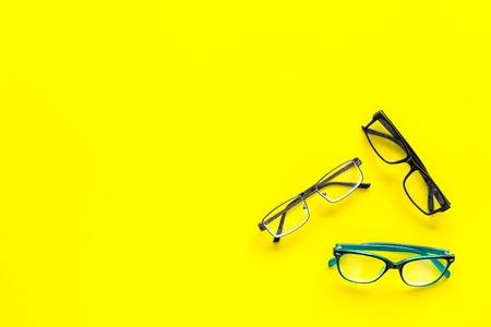 Glasses concept. Set of glasses with different eyeglass frame and transparent lenses on yellow background top view.