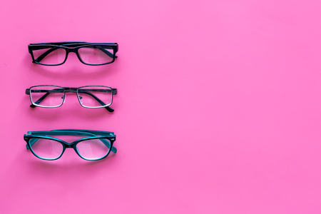 Glasses concept. Set of glasses with different eyeglass frame and transparent lenses on pink background top view. Reklamní fotografie - 103681668