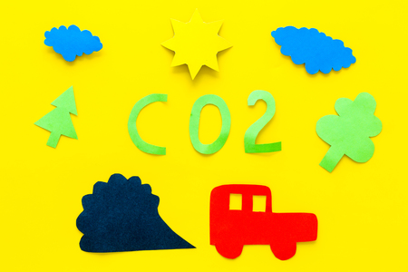 Cars emitting carbon dioxide. Pollution concept. harm the environment. Car and smoke cutout on yellow background top view Archivio Fotografico - 103862677