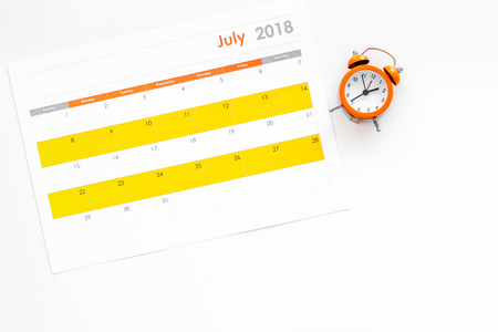 Deadline concept. Alarm clock on calendar on white background top view copy space 版權商用圖片