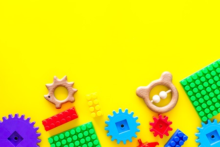 Developing children games mockup. Colorful plastic bricks and blocks on yellow background top view space for text