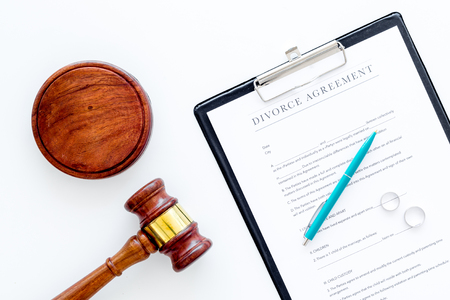 Divorce court case. Divorce agreement near wedding rings and judge gavel on white background top view