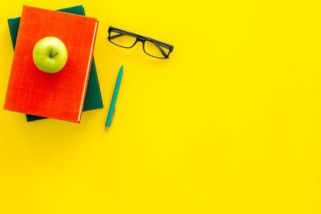 Educational literature. School textbook, book, tutorial, apple and glasses on yellow background top view copy space