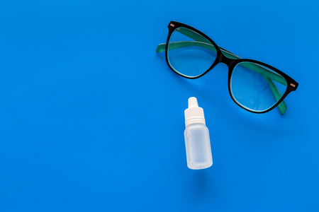 Eye drops in small bottle near glasses on blue background top view copy space