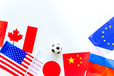 Football championat. American, Canadian, European, Japanese, China, Russian flags and football ball on white background top view copy space